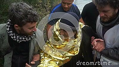 LESVOS, GRIECHENLAND - 5. NOVEMBER 2015: Freiwillige helfen altem Flüchtling, auf Ufer zu gehen
