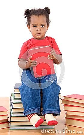 Lettura del bambino che si siede su un mucchio dei libri
