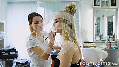Letztes Schliff Im Salon für schöne Blondinen tun Sie Make-up Maskenbildner malt ihre Lippen, erhöht die Menge von stock footage