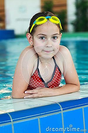 Schoolmeisje met beschermende brillen in zwembad