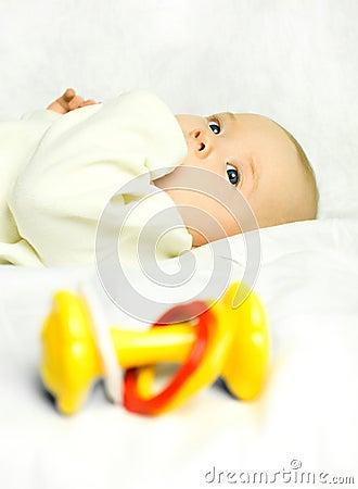 Leuke baby op het bed met een stuk speelgoed