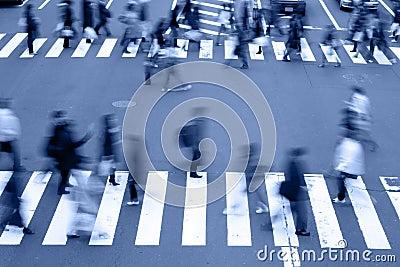 Leute, welche die Straße-blauen Töne kreuzen