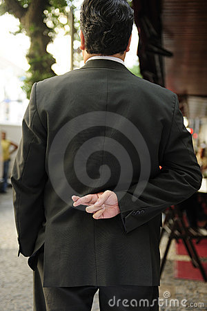 Liar: businessman with fingers crossed