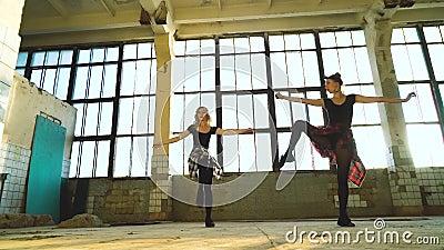 Liebliche Tänzer, die im alten Fabrikgebäude Beinübungen machen stock video