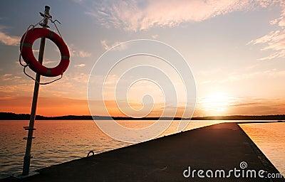 Lifebuoy on the pier in the orange sunrise