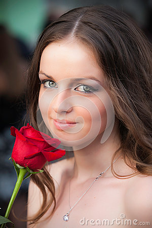 Lifestyle portrait of young woman with red rose