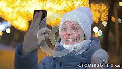 Lifestyle, una turista, comunica con la sua famiglia in un video - chiamata in un parco invernale contro una garland stock footage