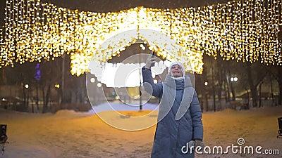 Lifestyle, una turista, comunica con la sua famiglia in un video - chiamata in un parco invernale contro una garland archivi video