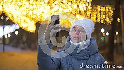 Lifestyle, una turista, comunica con la sua famiglia in un video - chiamata in un parco invernale contro una garland video d archivio
