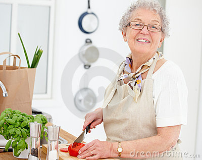 Lifestyle - Woman smiling and chopping tomatoes