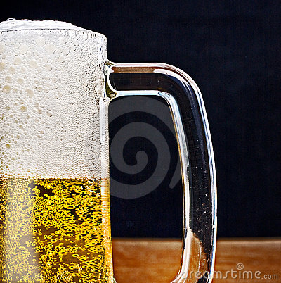 Light Beer in a glass pint mug served on a wooden
