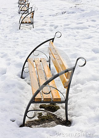 Light brown wooden benches on snow