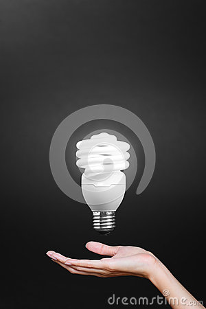 Light bulb in hand with gray background