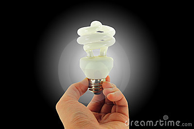 Light Bulb In Hand Isolated On Black And Spotlight