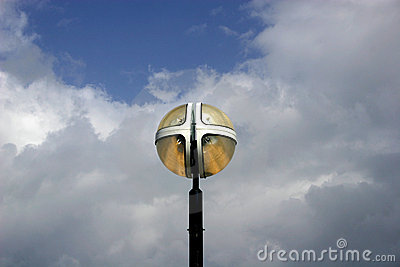 Light fixture against white clouds and blue sky
