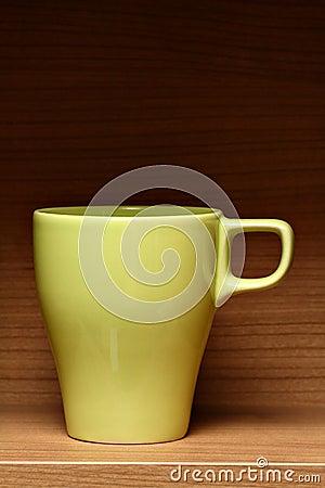 Light green coffee cup on wooden shelf