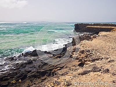 Light green ocean surf and rocky shore