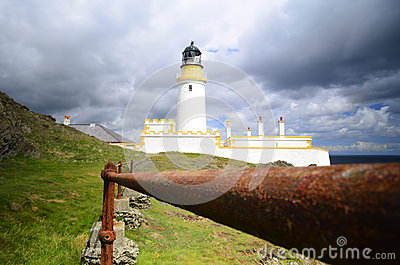Lighthouse on cliff edge behind old rusty fence bars