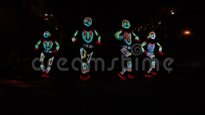 Light show group. Presentation of dancers in light costumes on stage