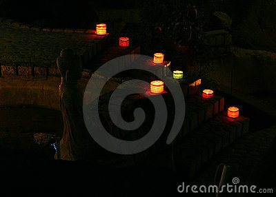 Lighted colored lamps and candles with Buddha