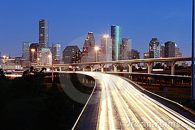 Lighted Houston skyline against blue sky