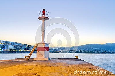 Lighthouse of Agios Nikolaos city at sunset