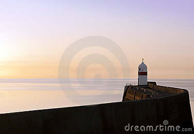 Lighthouse with breakwater wall at sunrise
