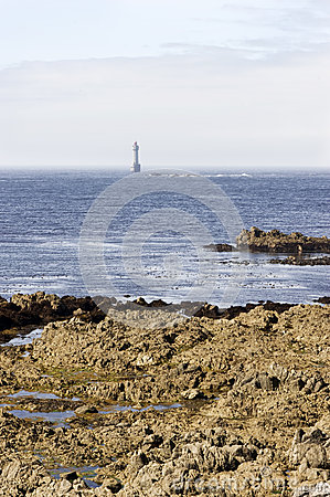 Lighthouse by the coast in Britain with clouds