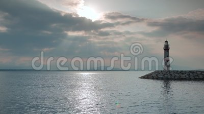 Lighthouse on a sea coast under the sun rays and stock video footage