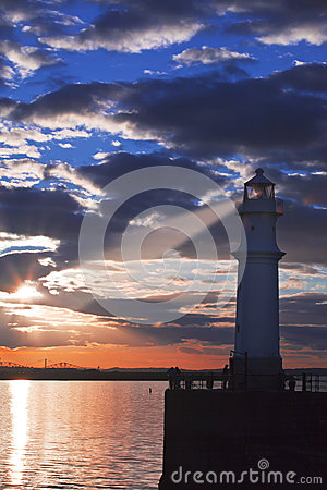 Lighthouse at sunset with light beam