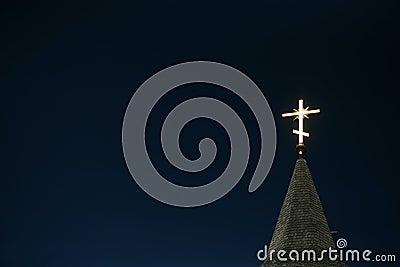 Lighting orthodox cross on a blue sky