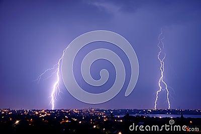 Lightning strike over dark blue sky in night city