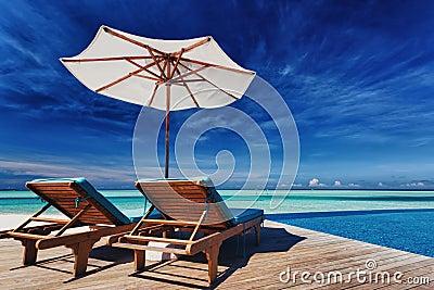 Ligstoelen en oneindigheidspool over tropische lagune royalty vrije stock afbeeldingen - Ligstoelen en merisier ...