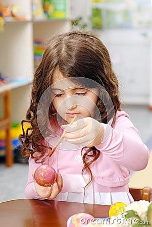 Liile girl paints an Easter egg