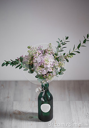 Free Lilac Flower In A Green Vase On Wooden Background Royalty Free Stock Image - 72964286