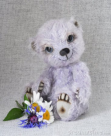 Lilac teddy-bear with a bunch of flowers at feet