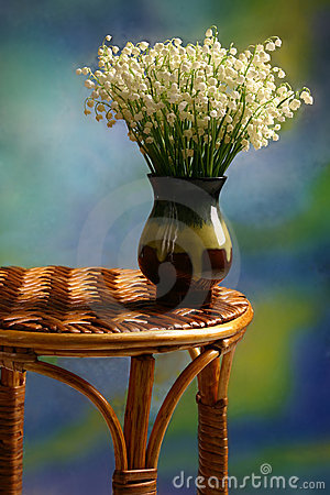 Lilies of the valley in the vase stay on the wicker table