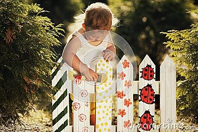 Lilla flickan målar ett staket