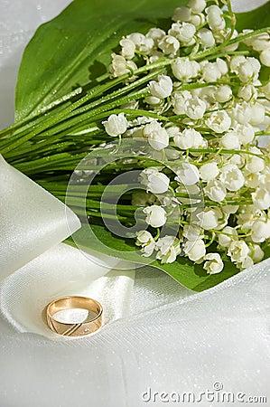 Lily-of-the-valley ed anello di cerimonia nuziale