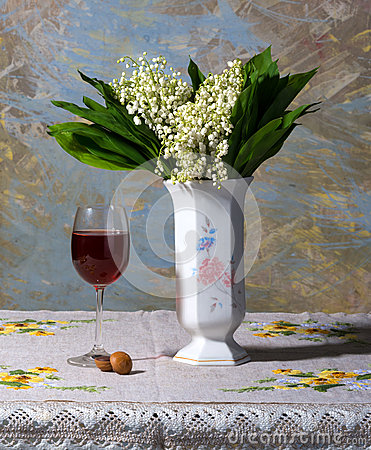 Lily of the valley in vase, glass of wine and candies