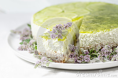 Lime cheesecake decorated with mint flowers, blurred background