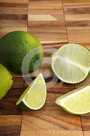 Limes and lime slices on a wooden pad