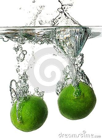 Limes splashing into Water