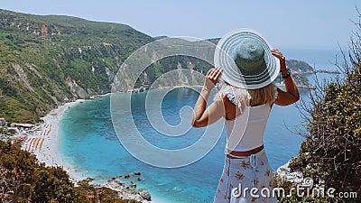 Lindas mulheres loiras que seguram chapéu de sol em brisa de vento no mar, desfrutando da visão da costa da ilha de Kefalonia, Gr filme