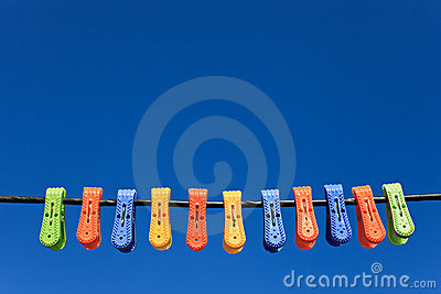 Line of multicolor plastic clothes pegs