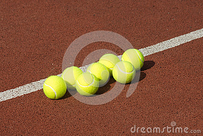 Line of seven yellow tennis balls on court