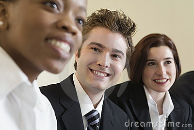 Line of three smiling business people at meeting.