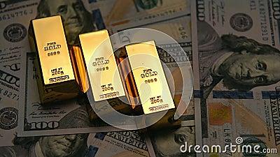 Lingotes y dólares del oro en una tabla con oscuridad al efecto brillante almacen de video