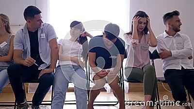 Linguagem corporal, grupo de jovens com as emoções diferentes que sentam-se na fileira em cadeiras durante a entrevista vídeos de arquivo