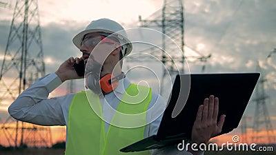Linhas elétricas e um técnico masculino com um portátil que fala em um telefone perto deles video estoque